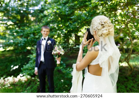 Bride shooting of her fiance in a park - stock photo