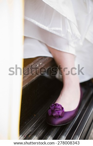 Bride showing off her purple shoes under her wedding dress