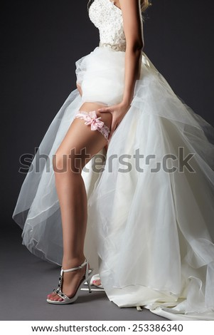 Bride shows her tanned slim leg with garter - stock photo