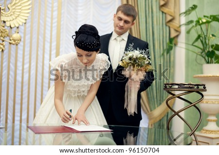 Bride signing her wedding license. Groom stands near