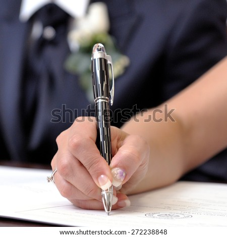 Bride signing the marriage certificate after the wedding