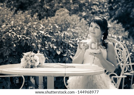 Bride sitting at a table of summer cafe