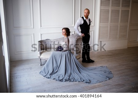 bride sitting on the vintage couch, groom standing near by her in a white room, the bride in a gray dress with lace, groom with red beard in black trousers, white shirt and black vest - stock photo