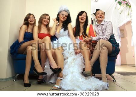 Bride sitting with girlfriends in professional fashion designer studio - stock photo