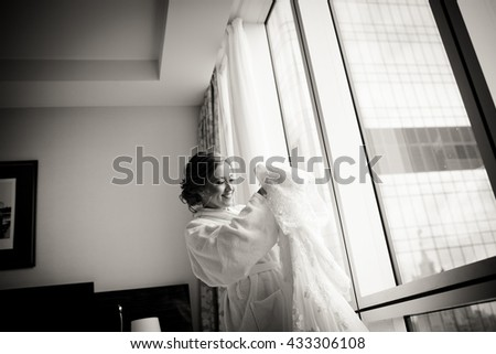 Bride smiles holding a rich wedding dress in her arms - stock photo