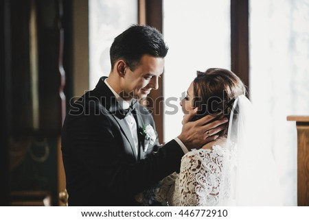 Bride smiles to a groom while he holds her happy face in his arms