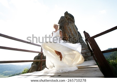 Bride spins between the mountains against the sky - stock photo