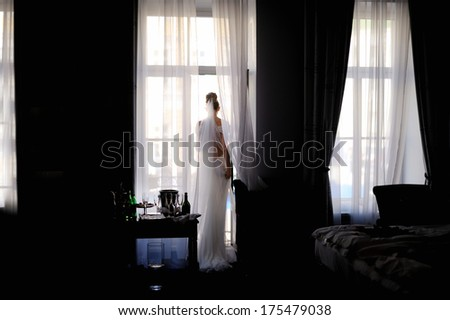 Bride standing against the window looking outside