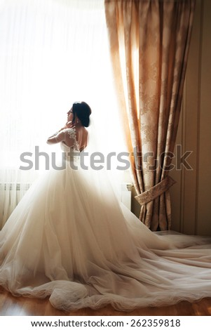 bride standing at the window. sunny day - stock photo