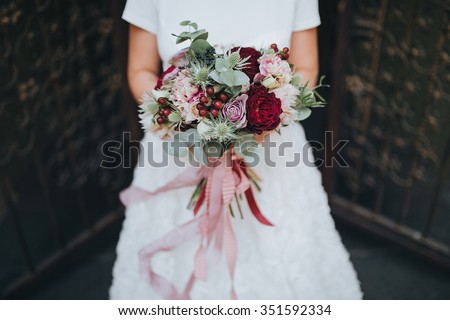 Bride standing on a dark background and holding a bouquet of pink flowers, white flowers and greenery with a pink ribbon