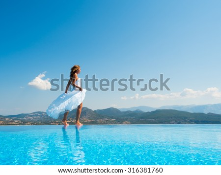 Bride standing on the edge on the infinity pool in Greece