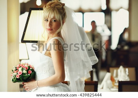 Bride stands in the front of the window in a restaurant - stock photo