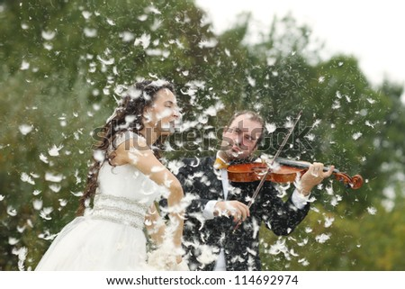 bride throwing feathers while groom sings on the violin - stock photo