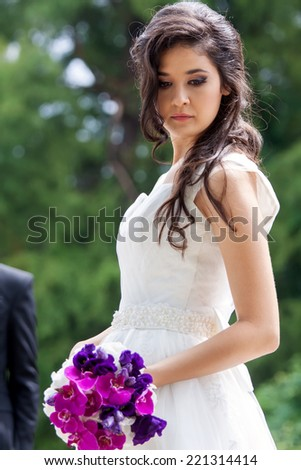 Bride waiting her groom in the park - stock photo