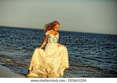 Bride walking along the beach wearing beautiful wedding dress - stock photo