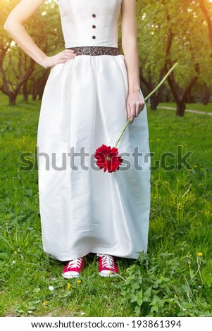Bride wearing red sneakers holding a flower in summer park - stock photo