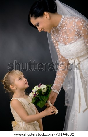 Bride wearing romantic white wedding dress with veil, giving bouquet of flowers to little bridesmaid, smiling.?