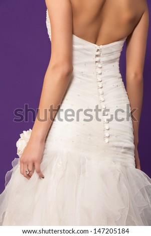 bride wearing silk dress - closeup on the button details on her back and the ruffles skirt  - stock photo