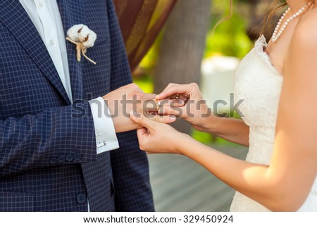 Bride wearing wedding ring on groom`s finger close-up picture