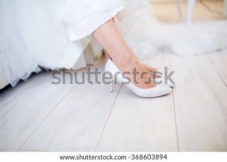 Bride wearing wedding shoes - stock photo