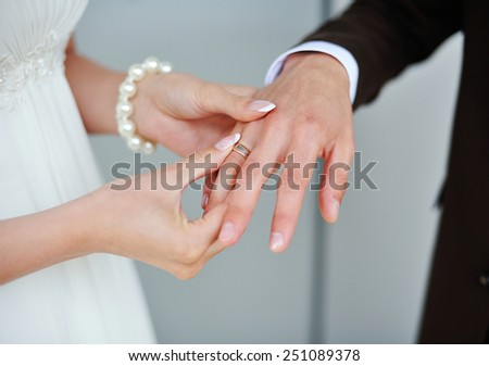 bride wears a gold ring to the groom wedding. - stock photo