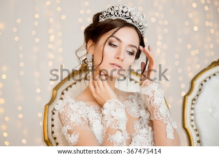 Bride. Wedding. The bride in a short dress with lace in the crown earrings. Wedding bouquet, makeup, hairstyle. Wedding Style - stock photo