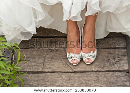 bride white open toe shoes decorated with bow and strass on wood boards - stock photo