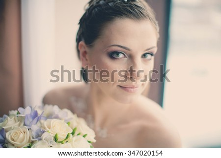 bride with a bouquet at a window - stock photo