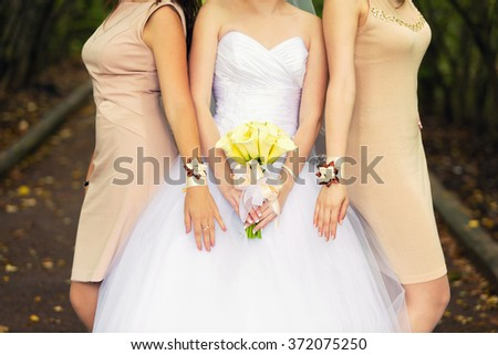 bride with a bouquet of yellow callas and bridesmaids in beige dresses - stock photo