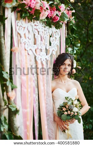 Bride with a wedding bouquet. Arch