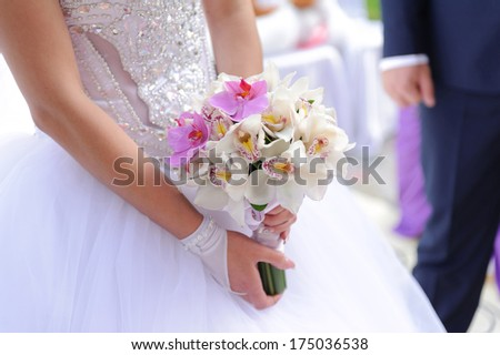 bride with beautiful orchid wedding bouquet - stock photo