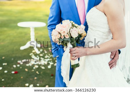 bride with bouquet of pink flowers and groom in blue suit together on wedding ceremony - stock photo