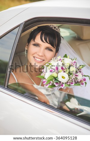 Bride with bouquet sitting in the car - stock photo