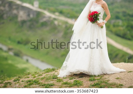 bride with bouquet standing on hill