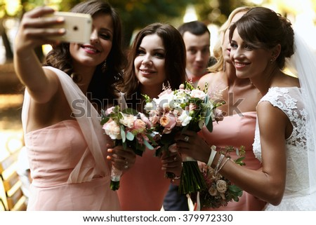 Bride with bridesmaids on the park on the wedding day - stock photo