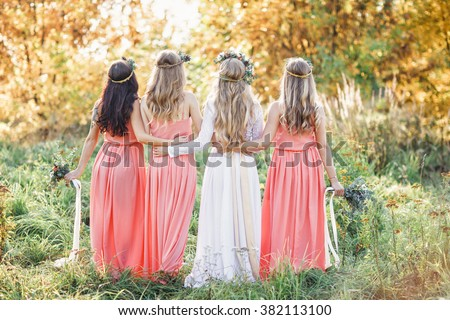 Bride with bridesmaids outdoors - stock photo