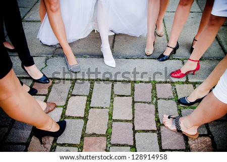 Bride with girlfriends, close to his feet