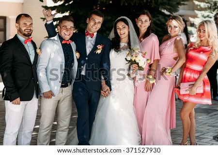 Bride with groom, guests and bridesmaids at  wedding ceremony outdoors - stock photo