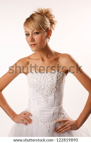 Bride with her hands on waist is looking at camera