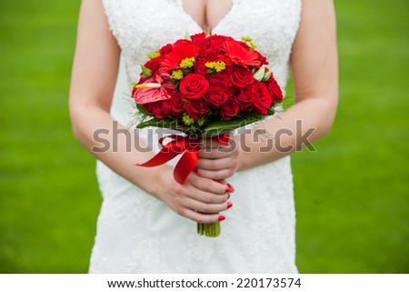 Bride with red wedding bouquet in hand - stock photo