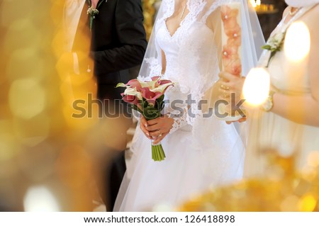 bride with wedding bouquet at church ceremony - stock photo