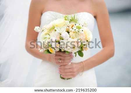 Bride with wedding bouquet in hand - stock photo
