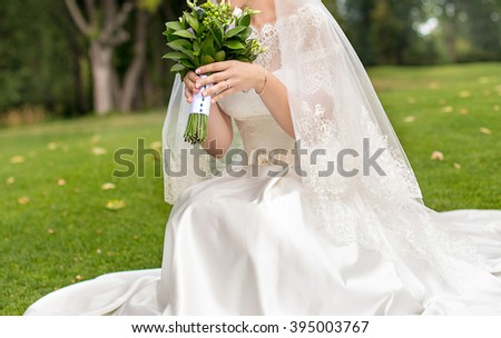 Bride with white dress sitting on green grass and holding her bouquet