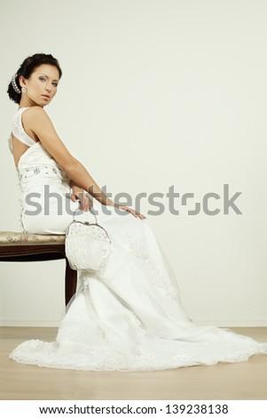Bride with white wedding change purse - stock photo