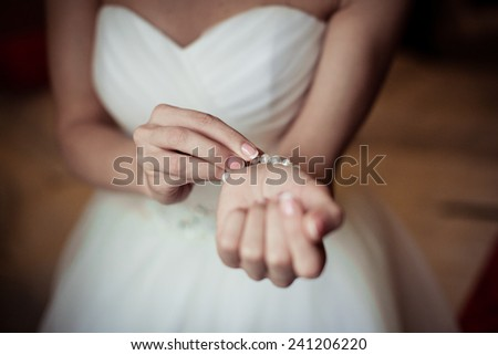 bride wrapping pearl bracelet on hand  - stock photo