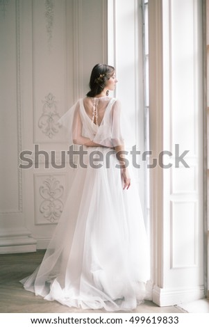 Bride. Young women with wedding dress in very bright room, some fine film noise effect added