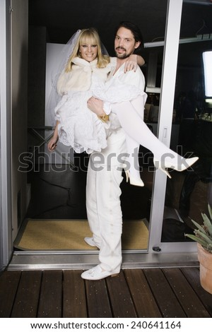 Bridegroom Carrying Bride Over Threshold of New Home - stock photo
