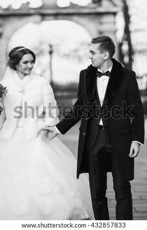 Bridegroom holds bride's hand during the walk in the park