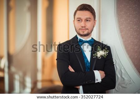 Bridegroom preparing for the wedding, straightens his shirt sleeves - stock photo