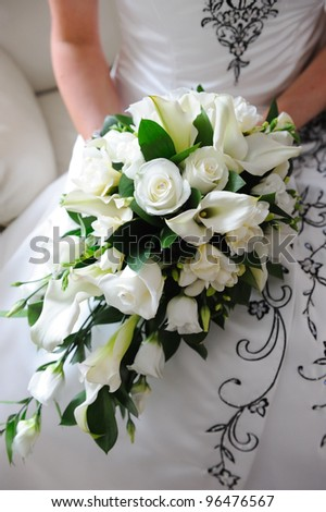 Brides bouquet is white roses. - stock photo